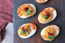 Horizontal image of deviled eggs with chipotle on a slate with a red towel
