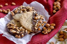 Three chocolate-coated peanut butter cookies on a piece of parchment paper on top of a gathered red cloth with scattered honey roasted nuts.