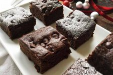 Horizontal image of chocolate gingerbread bars on a white tray with some dusted on top with powdered sugar.