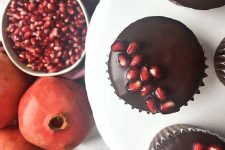 Horizontal image of a cupcake on a white plate with pomegranates and seeds on the side.