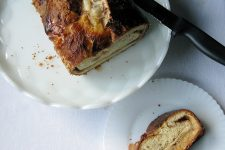 Top view of cinnamon swirl bread on white plates on top of a white counter.