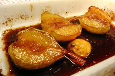 A close up view of roasted apples and pears with cinnamon sauce in a white plate