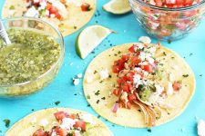 Chicken tacos with salsa and cheese on corn tortillas, with dishes of green and red salsa, lime wedges, and scattered finely chopped cilantro on a light blue background.