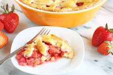 A piece of strawberry rhubarb pie is on a white square-shaped plate with rounded edges, alongside a fork, with the rest of the pie in a yellow-orange ceramic dish at the top of the frame, and several whole red strawberries with green tops scattered to the left and right on a white marble surface.