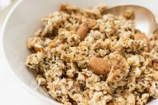 Horizontal close-up image of a white bowl with granola with nuts and chia seeds.