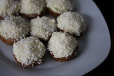 A top view image of coconut cupcakes with coconut flakes on top.