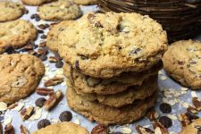 Horizontal image of a stack of baked treats surrounded by nuts and chocolate.