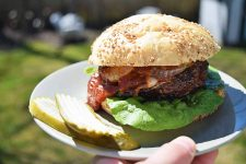 A cheeseburger with lettuce, barbecue sauce, and grilled onions, on a sesame seed bun, on a white plate next to a few pickle chips, with a hand holding the plate up to the camera, and a green lawn in soft focus in the background.