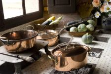 Copper pots and skillets on old wood stove next to lighted window