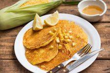 Enjoying a plateful of sweet cornmeal pancakes made with fresh corn. | Foodal.com