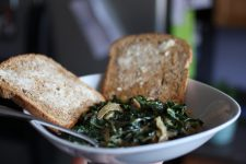 A close up image of a bowl filled with collard greens and two pieces of bread on the side.