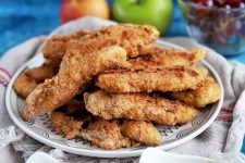 Horizontal image of a plate of stacked chicken fingers on a towel with apples and grapes.