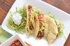 Horizontal overhead shot of three beef tacos with lettuce and tomato on a plate, beside a pile of greens topped with a dollop of scallion and cilantro crema, on a brown wood table with a multicolored cloth and a small square dish of pico de gallo.