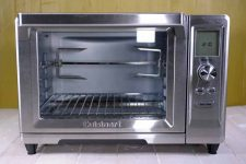 The Cuisinart TOB-200N Rotisserie Convection Toaster Oven on an olive green background.