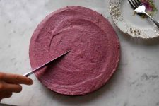 Top down view of a Dairy-Free Raw Berry Cream Pie with a Gluten-Free Chocolate Crust on a white, marble countertop.
