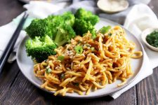Horizontal image of a white dish with pasta with a brown sauce next to broccoli florets.