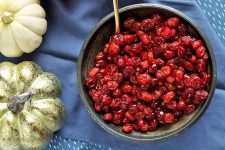 Overhead shot of a large gray serving bowl of roasted cranberries with a gold spoon, on a blue cloth with a miniature white and a gold artificial pumpkin to the left.
