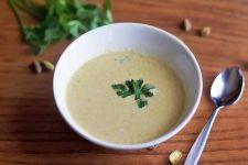 A white bowl of homemade cream of pistacho soup with a fresh herb garnish and a spoon to the right, with a sprig of flat-leaf parsley and scattered on nuts on a brown wood surface.