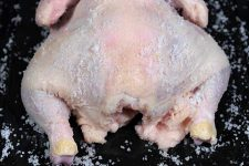 Close up of a whole chicken carcass that has been covered in sea salt | Foodal