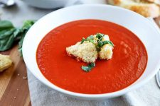Horizontal image of a white bowl of homemade tomato soup, garnished with cubes of toasted bread and chipped fresh basil, on a brown table topped with gray cloth placemats, and scattered bread and herbs.