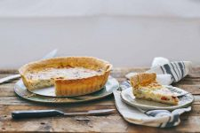 Horizontal image of a quiche with a golden crust, and a slice removed on a plate, all on a wooden table.
