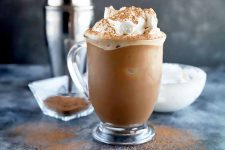 Horizontal image of a glass mocha drink topped with whipped cream and cocoa powder, next to a metal shaker, cocoa powder, and whipped cream.
