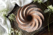 Horizontal top-down image of a whole bundt dusted with sugar on a wire rack, next to white flowers and white towel.