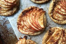 Horizontal top-down image of baked mini apple tarts with spices and granular sugar.