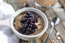 Oblique overhead horizontal image of a white dish of einkorn cooked porridge with roasted blueberries on top, on a wood surface that has not been painted or stained, topped with a crumpled white cloth, a spoon, a small glass dish of uncooked grain, and scattered slivered almonds and fruit.