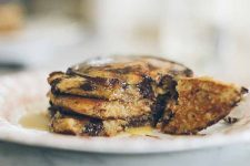 A stack of Einkorn Rye Chocolate Chip Pancakes on a dinner plate. Side profile view with a diffused background.