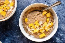 Horizontal image of breakfast bowls garnished with fresh mango chunks, coconut shreds, and chia seeds on a dark blue surface.