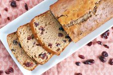 Overhead shot of a loaf of cranberry quick bread and three slices arranged on a rectangular white ceramic serving platter, on a patterned pink tablecloth topped with scattered dried berries.