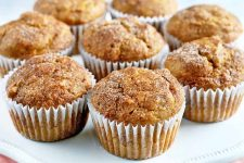 Eight pumpkin muffins with cinnamon and sugar topping arranged in a circle on a white plate.