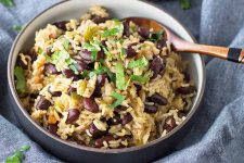Horizontal image of a wooden spoon inserted into a bowl of rice and beans garnished with herbs.