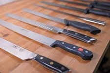 Oblique shot of a group of slicing and carving knives on a wooden table top. Selective focus.