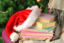 A Santa hat is arranged on top of a pile of books with pastel-colored covers, on a chair draped with a gray blanket with fringe, in front of a Christmas tree.