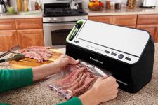 Human hands in a kitchen environment using the FoodSaver Vacuum Sealer V4440 2-in-1 Automatic System to seal up steak.