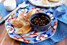 Horizontal image of a blue, white, and red plate of homemade chicken pot stickers with a soy and red chili dipping sauce in a small gray cup, with another white plate of appetizers in the background, and a small white ceramic cup and a pair of decorative chopsticks on a small blue ceramic fish rest to the left, on a blue cloth on top of a brown wood surface.