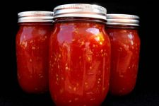 Three big jars of canned tomatoes, stewed, sauced, chopped. Home food canning and crafts or homemade style tomato recipes.