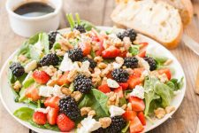 A fresh berry and spinach salad on a porcelain plate which is sitting on a rustic wooden table.