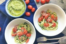 Horizontal image of two bowls with fresh zoodles and tomatoes with forks, a bowl of pesto, and whole tomatoes on a blue towel.