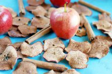 Homemade baked apple chips with three whole fruit and cinnamon sticks, on a blue background.
