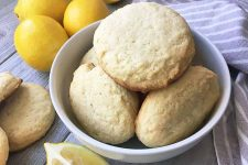 Horizontal image of a white bowl with a pile of freshly baked fluffy cookies surrounded by three whole lemons, lemon wedges, and a striped gray towel on a gray wooden surface.