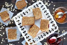 Homemade breakfast bars on a white serving dish and squares of parchment paper, with two bowls of red and orange jelly with spoons to the right, and scattered uncooked oats, on a dark brown wood surface.