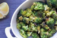 Overhead horizontal closely cropped image of roasted broccoli florets in a white ceramic serving dish with rounded edges and a ceramic handle, on a blue cloth surface with a wedge of fresh yellow lemon.