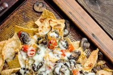Closeup of a brown baking pan of homemade nachos, on a wood background.