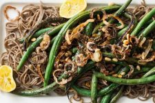 top down close up of a vegan-friendly and gluten-free side dish made with green beans, buckwheat soba noodles, and shallots.