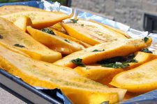 Sliced yellow summer squash marinated in vinegar and herbs, on a grill pan topped with foil.
