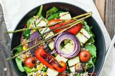 Horizontal image of a colorful charred vegetable salad in a dark plate.