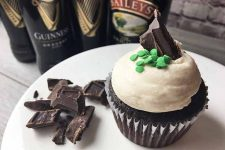 Horizontal image of a brown cupcake topped with white buttercream and chocolate/green sprinkle garnishes on a white plate with more garnishes, and bottles in the background.